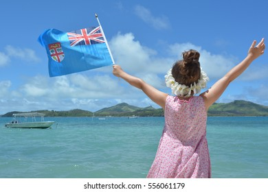 Young girl on family travel holiday vacation in Fiji waving the National flag of the Republic of Fiji. Real People copy space