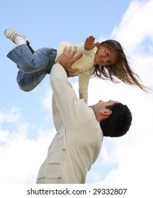 Young girl on father's arms at sky background