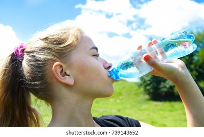 Young girl on a green lawn and drinks water
