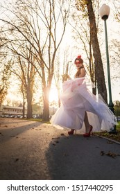 A young girl on a high heels in a wedding dress with a red lace mask, in an autumn park, with a saxophone in her hands.
