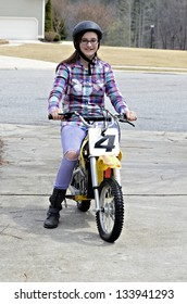 A young girl on a motorcycle.