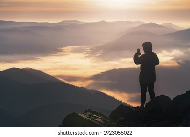 Young girl on the mountain peak photographs a beautiful mountain landscape at sunrise on the phone.