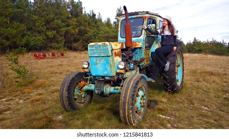 The young girl on the old abandoned tractor in The Crimea Mountains at Yalta Plateau in Crimea, Russia