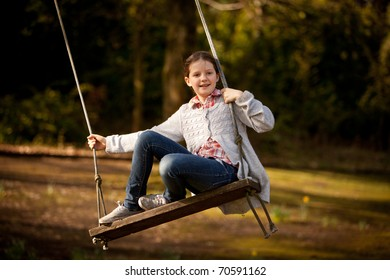 Young girl on an old wooden swing