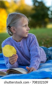 Young girl on a plaid in an autumn park