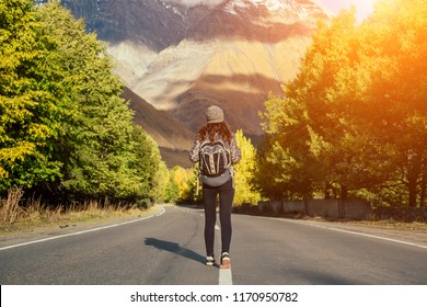 young girl on the road against the background of the mountains (hitch-hiking)