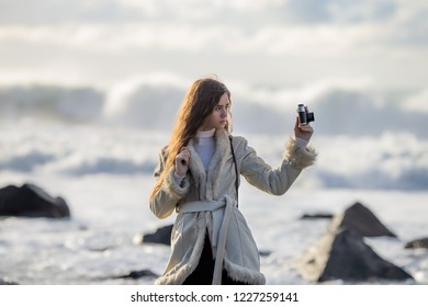 A young girl on the shore of a stormy sea is photographed on a tourist trip around Sakhalin Island walking along the shore admiring nature.
