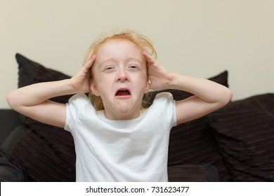 Young girl on sofa at home crying with hands on her head.