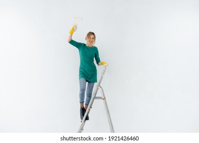 A young girl on the stairs paints a white wall with a roller. Repair of the interior.