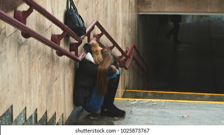 Young girl on the stairs in the subway depressed sitting alone obscures the face with his handsand crying. Autumn.