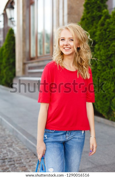 Young girl on a street walk. Street style portrait. Beautiful teenager in the city. Stylish girl weared in jeans and a red T-shirt. Life style. Summer. Make up for young blonde girl. Curled blonde
