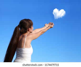 Young girl on a summer day launching the heart out of the cloud