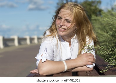 A young girl on a sunny day in a white blouse and black jeans poses on the waterfront. Nizhny Novgorod, Russia
