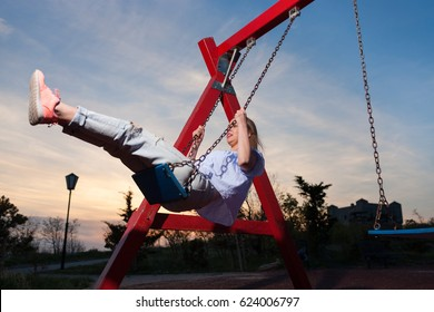 Young girl on the swing in the park at sunset.