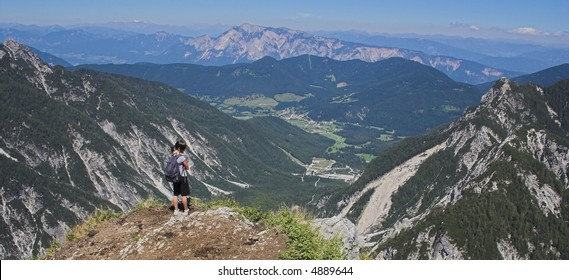 young girl on the top of a mountain (above a precipice, not visible on the photo), In the center is the giant ski-jump Planica (world's biggest with flight records over 230m); border triangle