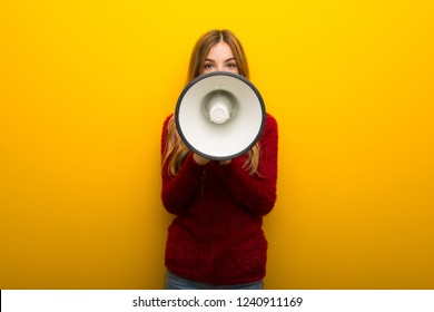 Young girl on vibrant yellow background shouting through a megaphone to announce something
