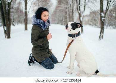 Young girl on walk with her dog on leash. Beautiful mistress sat down on her knees in front of her dog on winter road