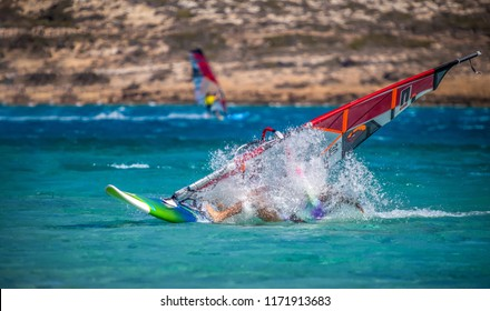 Young girl on windsurfing crashes in high speed with big splash of water in Chicken bay on Greece island of Karpathos