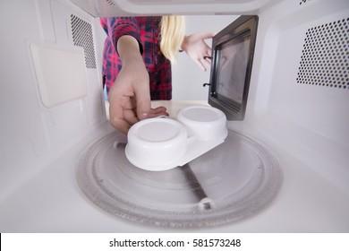 Young girl opening hand door microwave. Cooking egg poacher.
