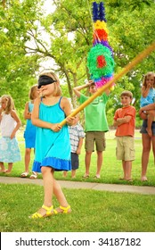 Young girl at an outdoor party hitting a pinata