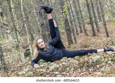 Young girl outdoors in the forest, engaged in shaping and posing. The overall plan, in gym. Russia.