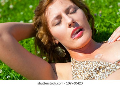 Young girl outdoors holding an ice cube in her mouth. Cold drops fall on her body. Heat concept.