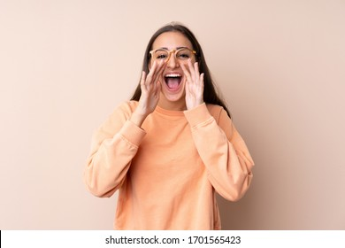 Young girl over isolated background shouting with mouth wide open