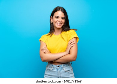 Young girl over isolated blue background keeping the arms crossed in frontal position