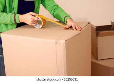 Young girl packing up and moving over the wall. Focus on hands with sticky tape