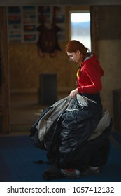 Young girl is packs a parachute indoors on a dark background close-up. Parachute packing.  Skydiving.