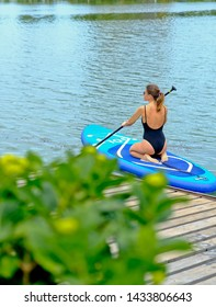 Young girl paddling on SUP board on a calm lake at city. Sup surfing woman. Awesome active training in outdoor. Lifestyle