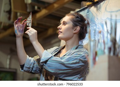 young girl painter examines a fragment of glass stained glass
