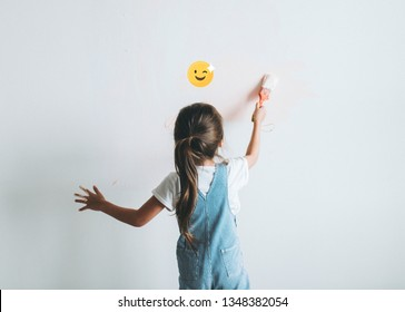 Young girl painting her bedroom walls