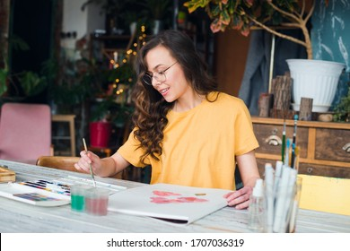 Young girl painting watercolors in her workplace