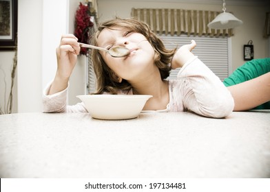 A young girl in pajamas eating breakfast at the table.