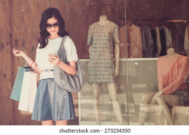 Young girl with paper bags standing at the shop window and text messaging