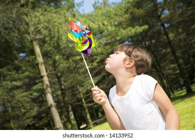 Young girl in park blowing on pinwheel.