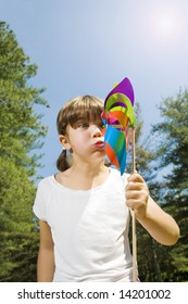 Young girl in park blowing on colored pinwheel.