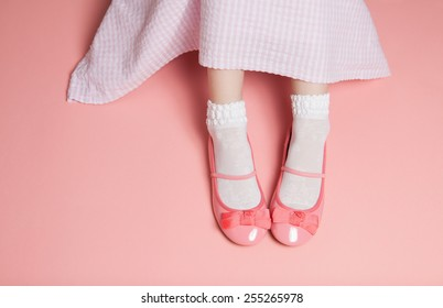 Young girl pastel pink outfit from above. Skirt and legs in white socks and flats shoes. Background layout with free text space.