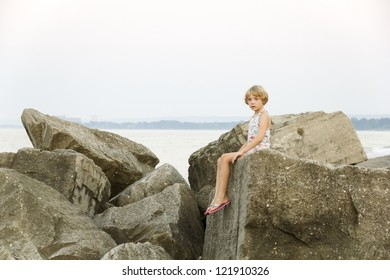A young girl pauses while playing on the lake side rocks, a brief haunting stare, troubled thoughts maybe?