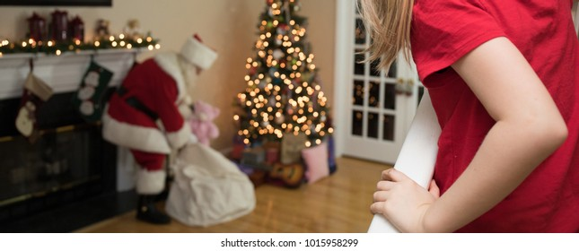 A young girl peeking around the corner discovers Santa in her living room on Christmas Eve.