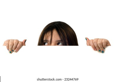 A young girl peeking over a white wall with her eyes looking at an upper corner