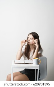 A young girl with a pen, notebook and a mug is thinking about the presentation, studying, speaking. One on a white background.