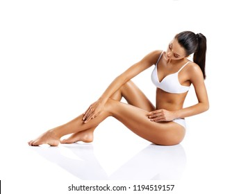 Young girl with perfect body touching her leg sitting on white background. Beauty & Skin care concept