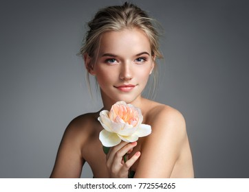 Young girl with perfect skin. Photo of blonde girl with rose on grey background. Skin care concept