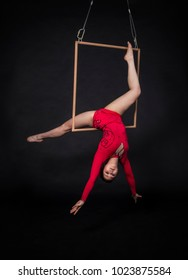 A young girl performs the acrobatic elements in the air trapeze. Studio shooting performances on a black background.