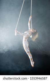 A young girl performs the acrobatic elements in the air trapeze. Studio shooting performances on a black background