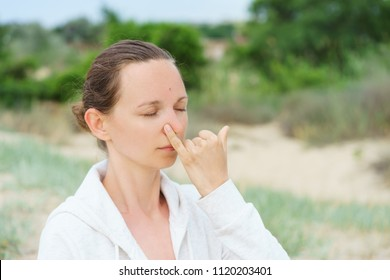 Young girl performs morning breathing practices of pranayama Nadi Shodhana on the beach in summer