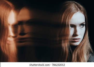 Young girl with personality disorder against black background with blurred face