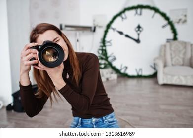 Young girl photographer shooting on studio. Professional photographer on work.
